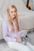 vonzó nő ül a mackó kezében szőnyeg