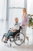 mladá žena tlačí invalidní vozík s starší žena v pečovatelském domě