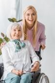 Fotografie mladé a starší ženy v invalidním vozíku s úsměvem a při pohledu na fotoaparát