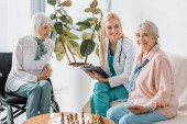 Fotografie mladá zdravotní sestra sedí na pohovce a psaní předpis pro starší ženy