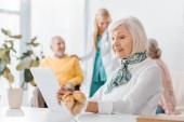 Starší žena pomocí digitálních tabletu v pečovatelském domě s rozmazané lidí na pozadí