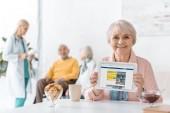 Starší žena zobrazeno rezervační aplikace na obrazovce digitální tabletu v pečovatelském domě
