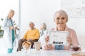 Starší žena zobrazeno airbnb aplikace na obrazovce digitální tabletu v pečovatelském domě