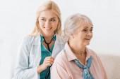 Fotografie mladá usměvavá lékařka s stetoskop starší žena