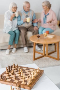 wooden chess desk with figures and blurred senior people at background