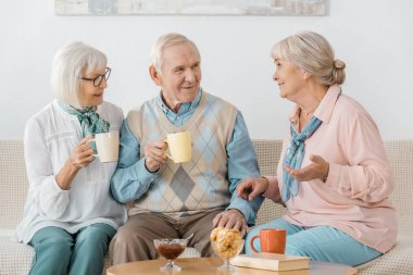 senior people drinking coffee and talking in nursing home