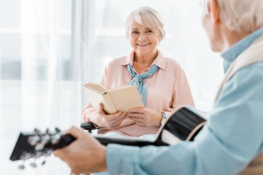 smiling senior woman with book listening senior man playing acoustic guitar