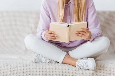 woman reading book and sitting on sofa with crossed legs