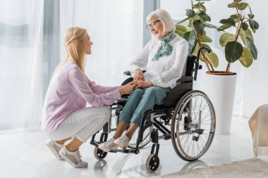 young woman speaking with senior woman in wheelchair at nursing home