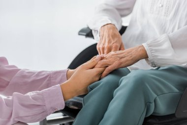 young and senior women holding hands in nursing home