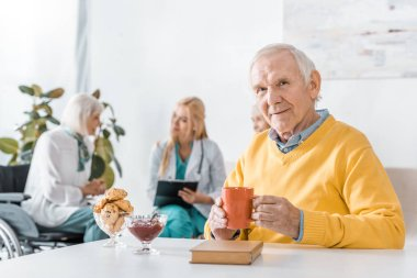 Senior man drinking tea while doctor examining senior women stock vector