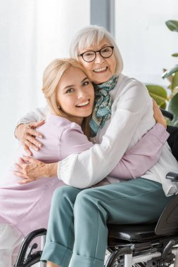 young cheerful woman hugging senior woman in wheelchair
