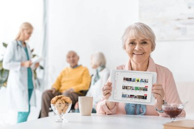 senior woman showing youtube channel on digital tablet screen at nursing home