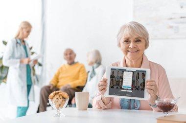 senior woman showing linkedin app on digital tablet screen at nursing home