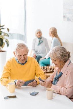 senior man and woman playing cards at table at nursing home