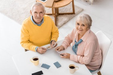 happy smiling senior couple playing cards at table at nursing home