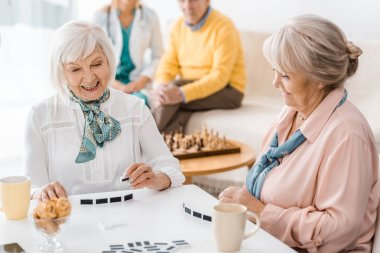 senior women playing domino at white table at nursing home