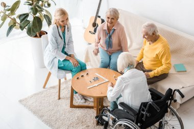 young female nurse playing domino with senior patients in nursing home