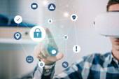 Fotografie Mann in Virtual-Reality-Headset zeigt auf Cyber-Sicherheitszeichen im Raum