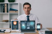 portrait of businessman showing laptop, tablet and smartphone with cyber security signs on screens at workplace in office