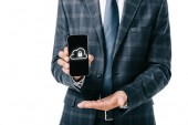 Fotografie oříznuté zastřelil podnikatel v obleku ukazující smartphone s cyber bezpečnostní cedulka na obrazovce izolované na bílém