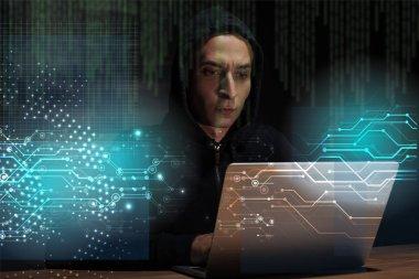 Portrait of hacker in black hoodie using laptop, cuber security concept stock vector
