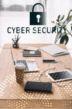 close up view of cyber security sign, workplace with laptop, coffee to go and notebook