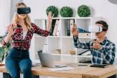 Fotografie junge Unternehmer in virtual-Reality-Headsets gestikulieren am Arbeitsplatz im Büro