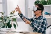 Fotografie Geschäftsmann in virtueller Realität Kopfhörer gestikulieren am Arbeitsplatz mit Laptop im Büro