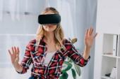 fiatal nő a virtuális valóság fejhallgató intett a szobában