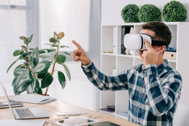 side view of businessman in virtual reality headset gesturing at workplace with laptop in office