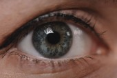 Fotografie Oříznout záběr ženské oko při pohledu na fotoaparát