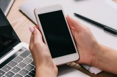 Schuss der Geschäftsfrau hält Smartphone am Arbeitsplatz mit Laptop zugeschnitten