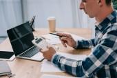 částečný pohled podnikatel s kalkulátorem pracovat na pracovišti s dokumenty a notebooky