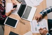 Oříznout záběr podnikatelé pracující na pracovišti s digitálními zařízeními a dokumenty