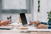 částečný pohled obchodníků s digitálními zařízeními pracující na pracovišti s doklady