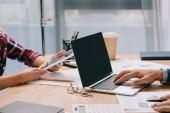 Fotografia vista parziale delle persone di affari con i dispositivi digitali che lavorano sul posto di lavoro con documenti