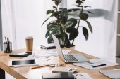 Fotografie zblízka pohled na pracoviště s laptop, tabulky, dokumenty a káva s sebou