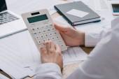 Oříznout záběr podnikatelka dělat výpočty na kalkulačce na pracovišti s dokumenty