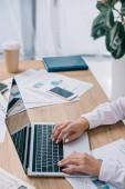 částečný pohled podnikatelka pracující na notebooku s prázdnou obrazovkou na pracovišti v úřadu
