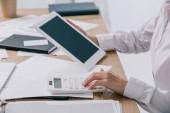 Oříznout záběr podnikatelka s tabletem, takže výpočty na kalkulačce na pracovišti s doklady v úřadu
