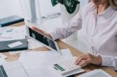 částečný pohled podnikatelka s tabletem kalkulací na pracovišti s doklady