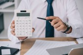 Fotografie partial view of businessman pointing at calculator in hand at workplace, accounting concept