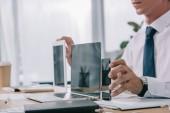 Fotografie oříznuté záběr podnikatel ukazuje notebook, tablet a smartphone s prázdnými obrazovkami na pracovišti v úřadu