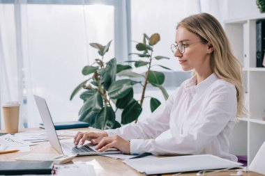 side view of businesswoman in eyeglasses working on laptop at workplace in office