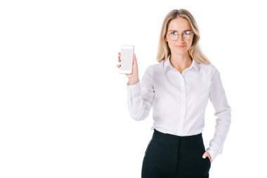 portrait of smiling businesswoman in eyeglasses showing smartphone with blank screen isolated on white