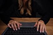 Fotografia vista parziale dellhacker femminile usando digitale portatile al piano in legno