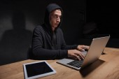 Photo hacker in black hoodie using laptops at tabletop with tablet in dark room, cyber security concept