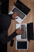 overhead view of hacker in black hoodie using laptops, cyber security concept