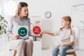 Fotografie adult psychologist showing happy and sad emotion faces cards to child